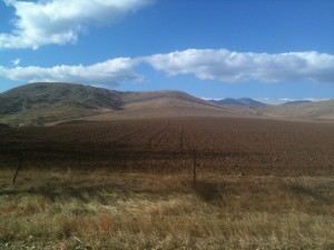 A recently plowed field with mountains in the background.